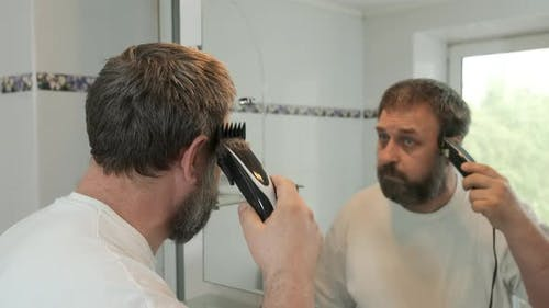 A man cuts himself with an electric hair clipper in the bathroom. Adaptation to souial distance.
