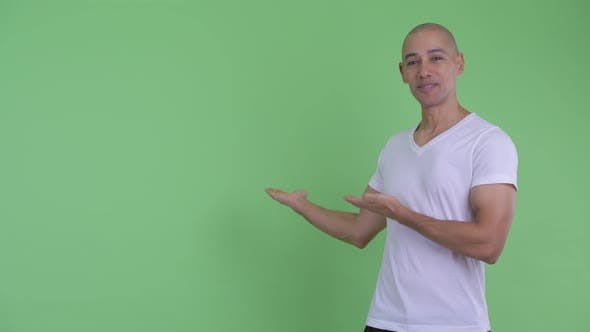 Thumbnail for Happy Handsome Bald Man Showing Something To the Back