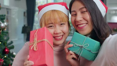 LGBTQ female teen relax happy holding Gift and using smartphone selfie with Christmas tree.