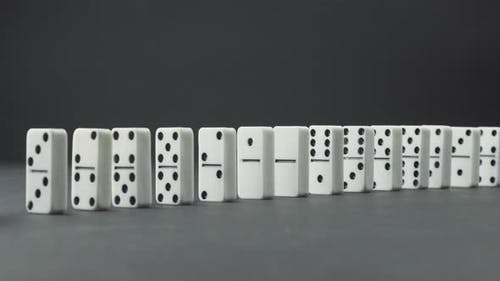 Domino Effect - a Series of Dominoes Falling Down the Chain Grayscale Image