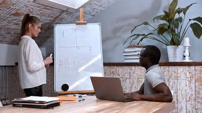 An Algebra Lesson - Woman Standing By the Board with Graphs of Functions and a Black Man Sitting By