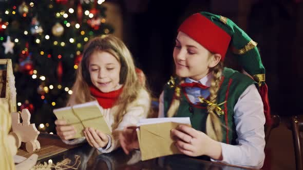 Thumbnail for Funny Elf is Sitting at the Table with a Little Girl and Showing How to Tie a Stack of Envelopes