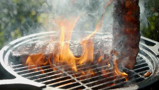 The Ribs Are Flipped on Grill with Fire and Smoke.