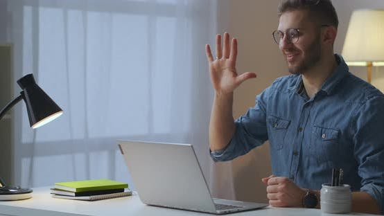 Thumbnail for Joyful Man Is Greeting Friends or Colleagues By Video Call in Laptop Internet Communication in Home