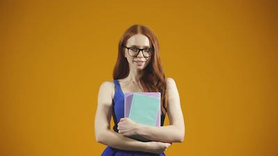 Portrait of a Young Student on an Isolated Background a Young Woman with Glasses Holding Books