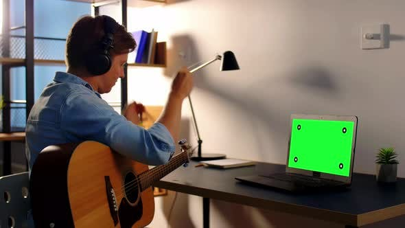 Thumbnail for Man in Headphones Playing Guitar at Home