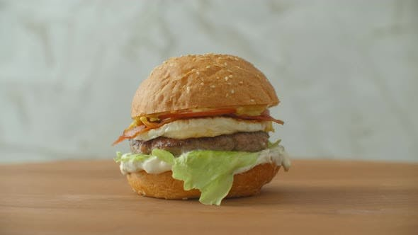 Thumbnail for A Big Tasty Burger with Meat Patty Onions Vegetables Melted Cheese Lettuce.