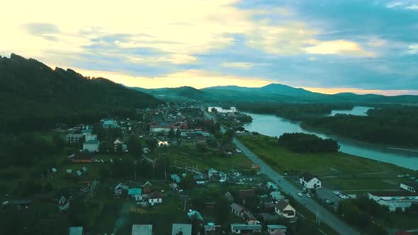 Thumbnail for Aerial View: Tourist City in the Mountains, in the Distance - a Mountain River. On the Sunset.