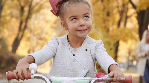 Porträt des kleinen lächelnden Mädchens auf dem Fahrrad im Herbstnachmittag