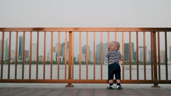 Cover Image for Baby Cute Dancing Holding Hands on the Railing on the Waterfront in the Background of the City