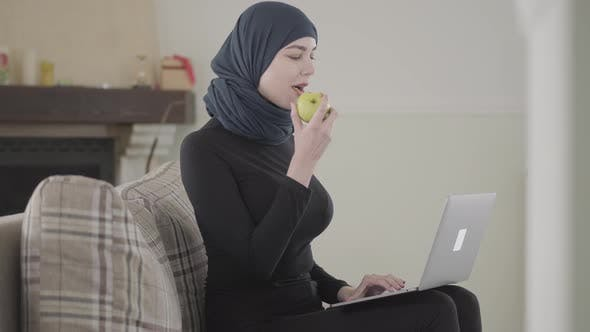 Thumbnail for Young Muslim Woman Was Working or Chatting By Laptop and Biting Juicy Apple Wearing Traditional