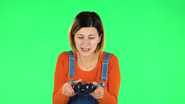 Cover Image for Girl Playing a Video Game Using a Wireless Controller with Joy and Loses. Green Screen