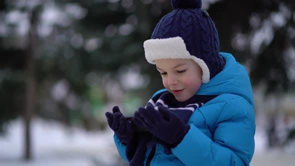 Kleiner Junge im Winter tragen mit Telefon an kalten verschneiten Tag