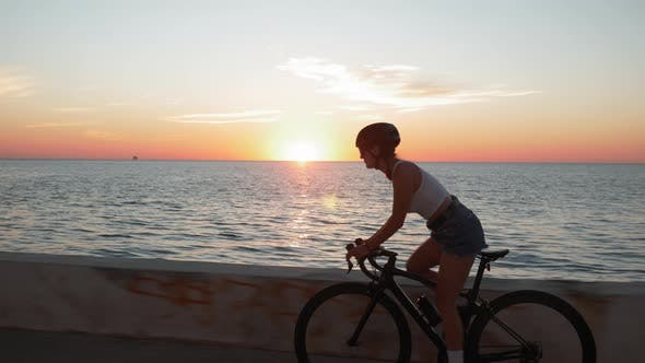 Thumbnail for Young stylish brunette woman rides bike on coastline at sunrise. Cycling at sunrise