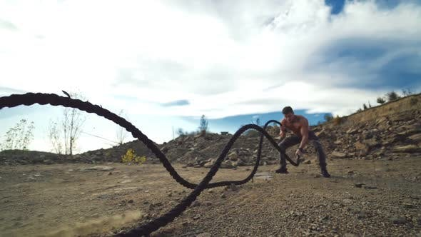 Sportsman exercising with battle ropes outdoors