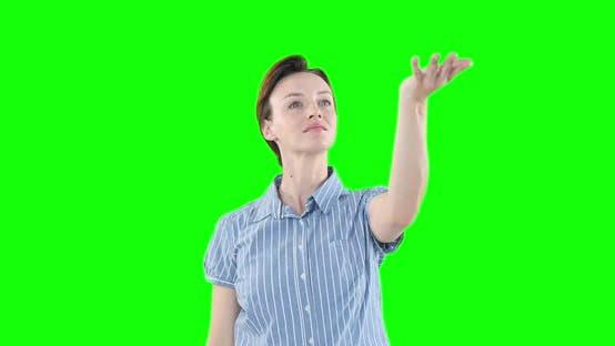 Caucasian woman raising hand on green background