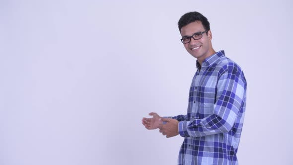 Happy Young Indian Hipster Man Showing Something To the Back