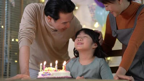 Kid blow candles with birthday cakes