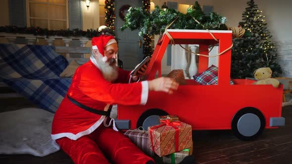 Thumbnail for Santa Claus Checking List of Presents on Tablet and Putting Gifts Into Car.