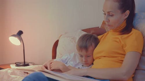 Mother and Son Reading a Book on the Couch Before Bedtime
