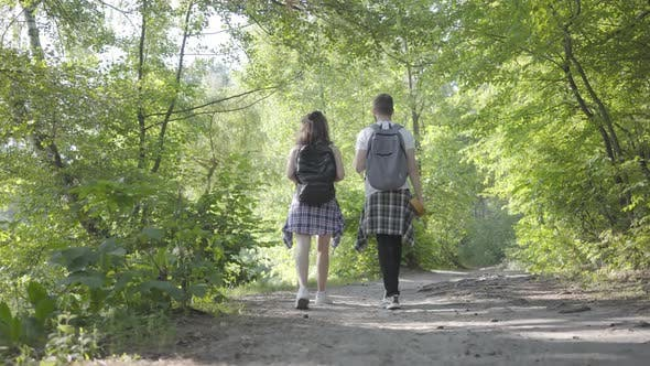 Thumbnail for Portrait of Guy and Young Cute Girl Walking in the Forest. Pair of Travelers with Backpacks Outdoors