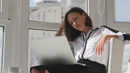 Concentrated upset female office manager sitting in modern office and looking at computer monitor