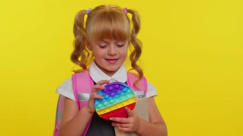 Funny Pupil Girl Playing with Pop It Sensory Antistress Toy Kid Presses on Colorful Squishy Bubbles