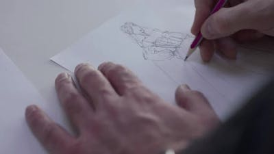 Top View of Male Designer's Hand Draws a Wedding Dress Sketch on Paper