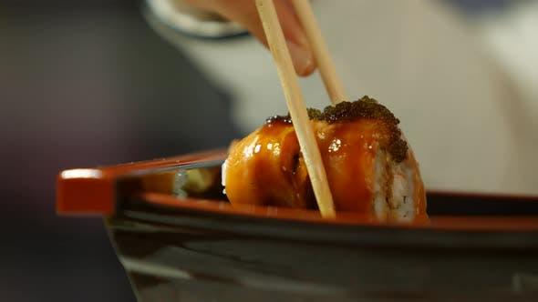 Hand with Chopsticks Taking Sushi.