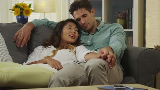 Thumbnail for Happy mixed race couple sitting on couch together