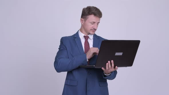 Thumbnail for Happy Bearded Businessman Thinking While Using Laptop