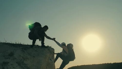 Silhouette of Helping Hand Between Two Climber. Two Hikers on Top of the Mountain, a Man Helps a
