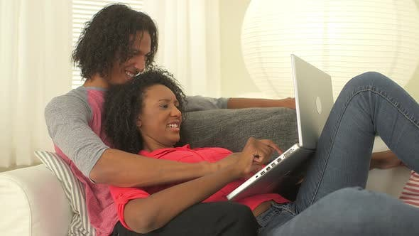 Thumbnail for Black teen couple using laptop on couch