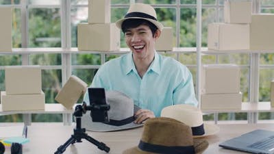 Smiling Asian man influencer reviewing fedora hat and selling a product online.