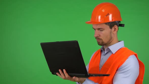 Thumbnail for A Young Handsome Construction Worker Works on a Notebook - Green Screen Studio