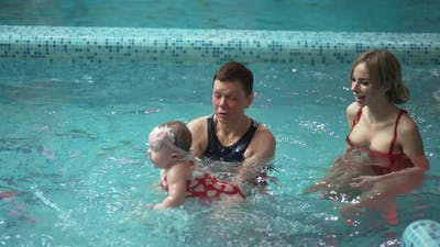 Instructor with a Small Child in the Pool