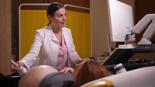 Woman Doctor Making Pregnancy Ultrasound in Clinic