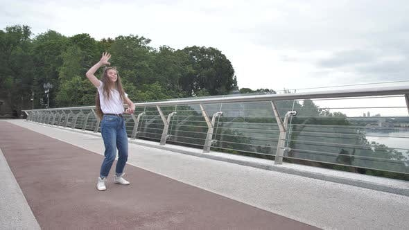 Beautiful Joyful Teenage Girl Dancing on Bridge
