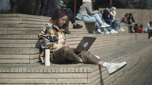 Woman Using Laptop While Sitting On Stairs