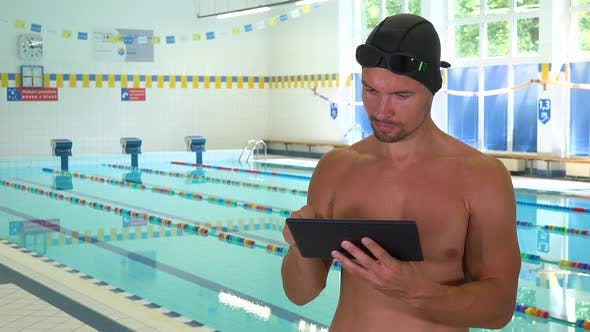 Thumbnail for A Professional Swimmer Works on a Tablet at an Indoor Pool