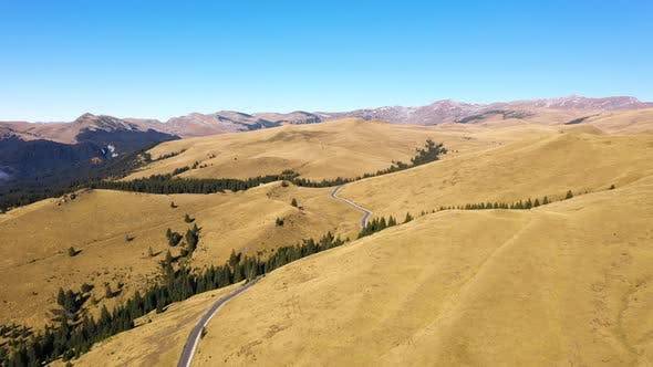 Aerial view of car driving down country road through rural rolling hills and mountain