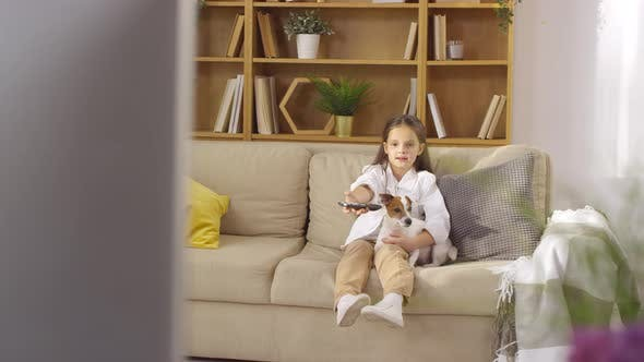 Thumbnail for Little Girl Sitting with Cute Dog on Sofa and Watching TV