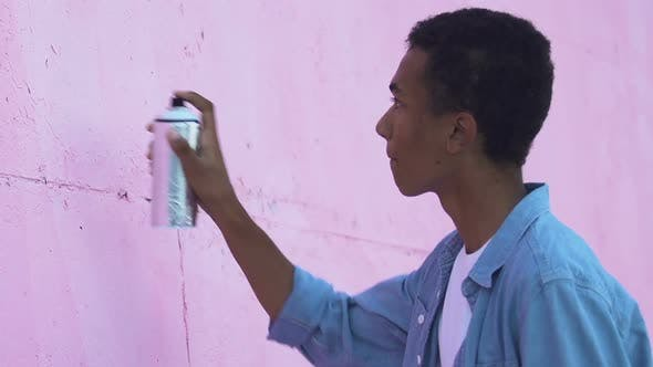 African-American male teenager painting piece sign on city wall