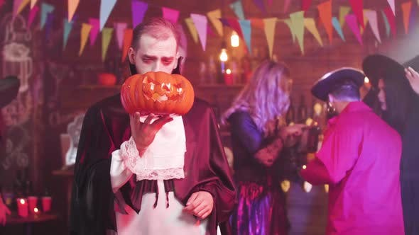 Man in a Ghoul or Vampire Costume Is Dancing with a Jack-o-lantern in His Hand