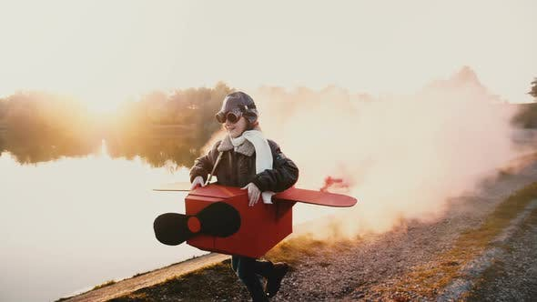 Thumbnail for Happy Little Pilot Girl Playing, Running Along Sunset Lake in Fun Cardboard Plane Costume with Color