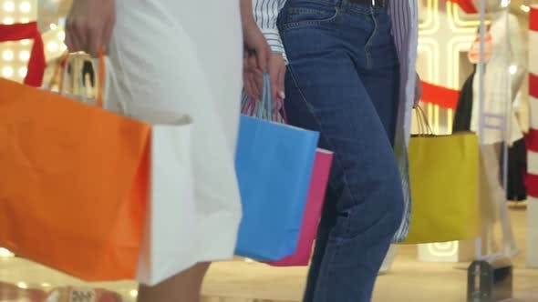 Thumbnail for Low Shot of Two Girls That Are Walking Through a Clothing Store in Colorful Garments