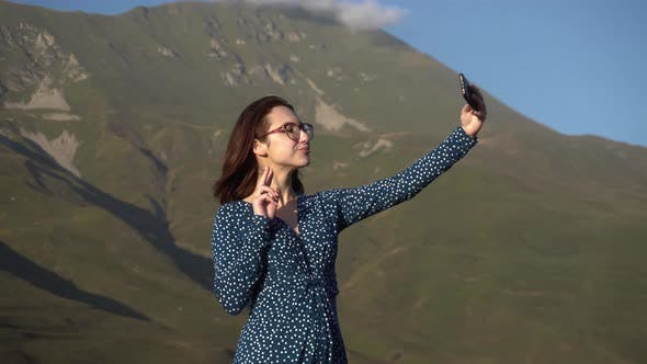 A Young Woman in a Dress Stands in the Mountains and Takes a Selfie on a Smartphone.