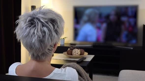 Eine Frau mittleren Alters beobachtet Out-of-focus TV in einem Wohnzimmer - Blick von hinten