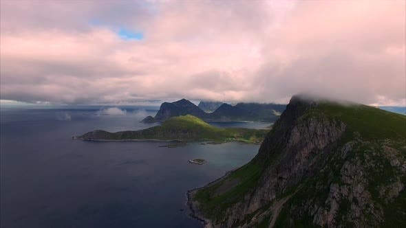 Flying in clouds by the cliffs on Lofoten islands, Norway