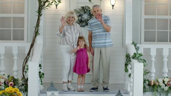 Thumbnail for Senior Grandfather and Grandmother Couple with Granddaughter Waving Hand, Smiling, Saying Hello